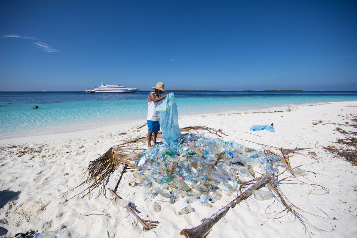 Chilean surfer Ramon Navarro collecting plastics on a beach in the Maldives. Photo: Corona and Parley for the Oceans